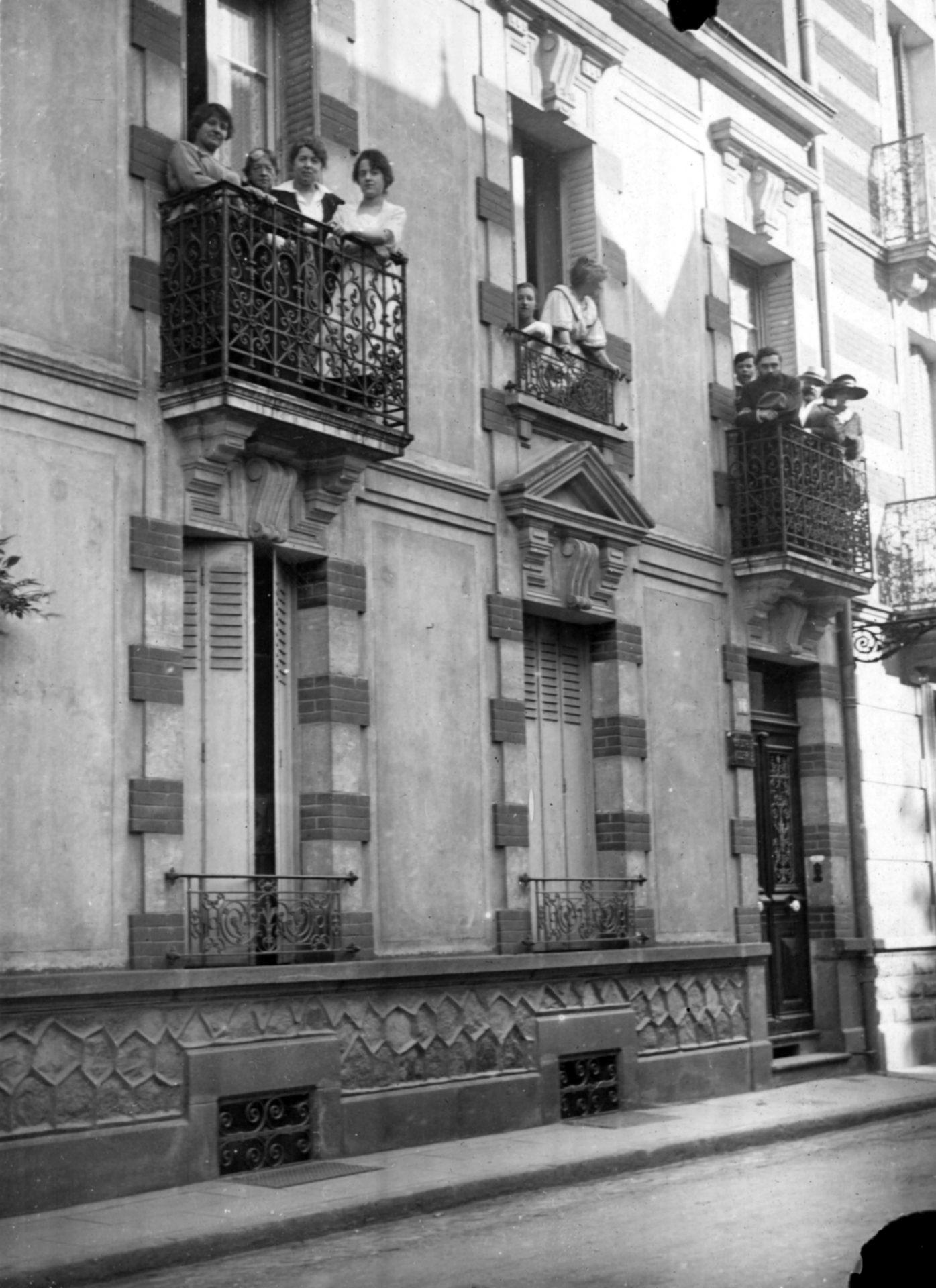 Groupe de personnes à un balcon, en compagnie d'Alexandre Varenne sur le balcon de droite.