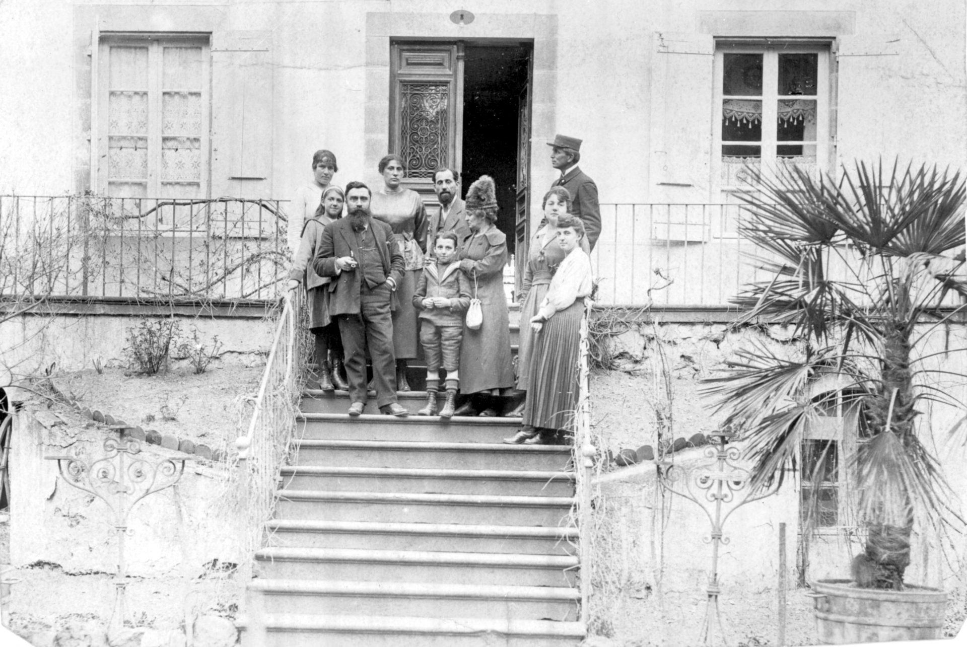 Groupe de personnes sur un escalier de maison en compagnie d'Alexandre Varenne à gauche