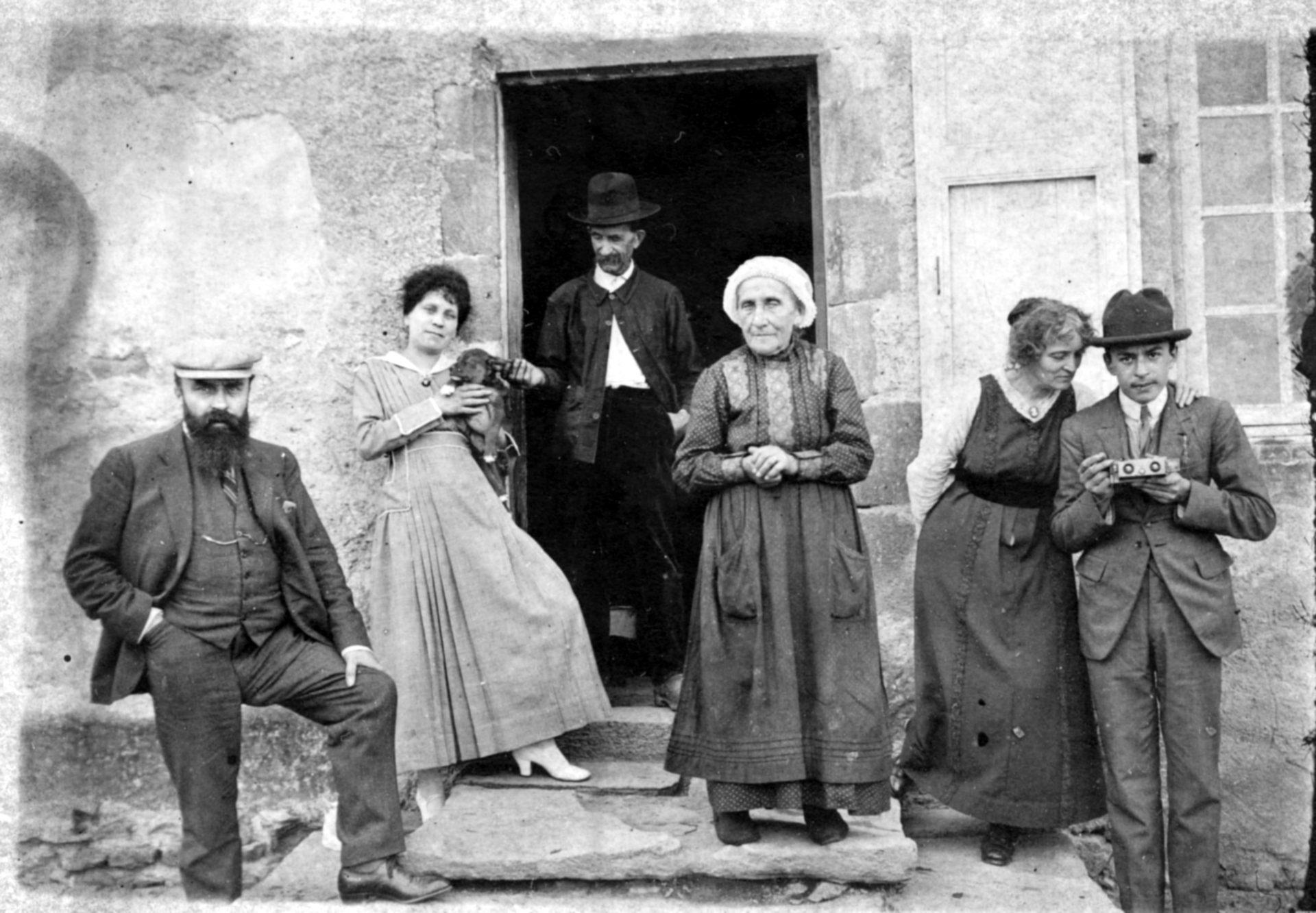 Groupe de personnes devant une maison en compagnie d'Alexandre Varenne à gauche