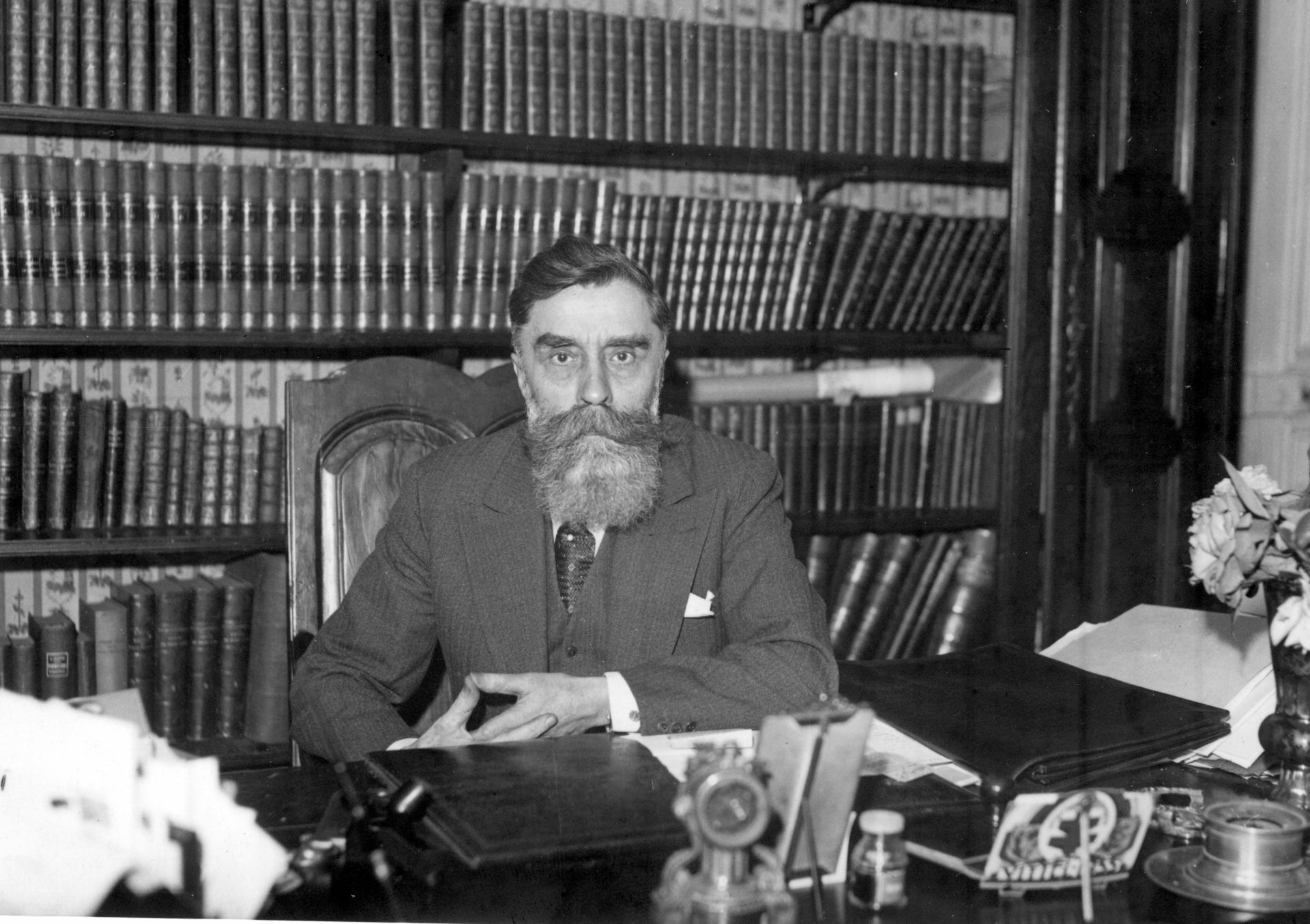 Alexandre Varenne assis à son bureau de travail devant sa bibliothèque