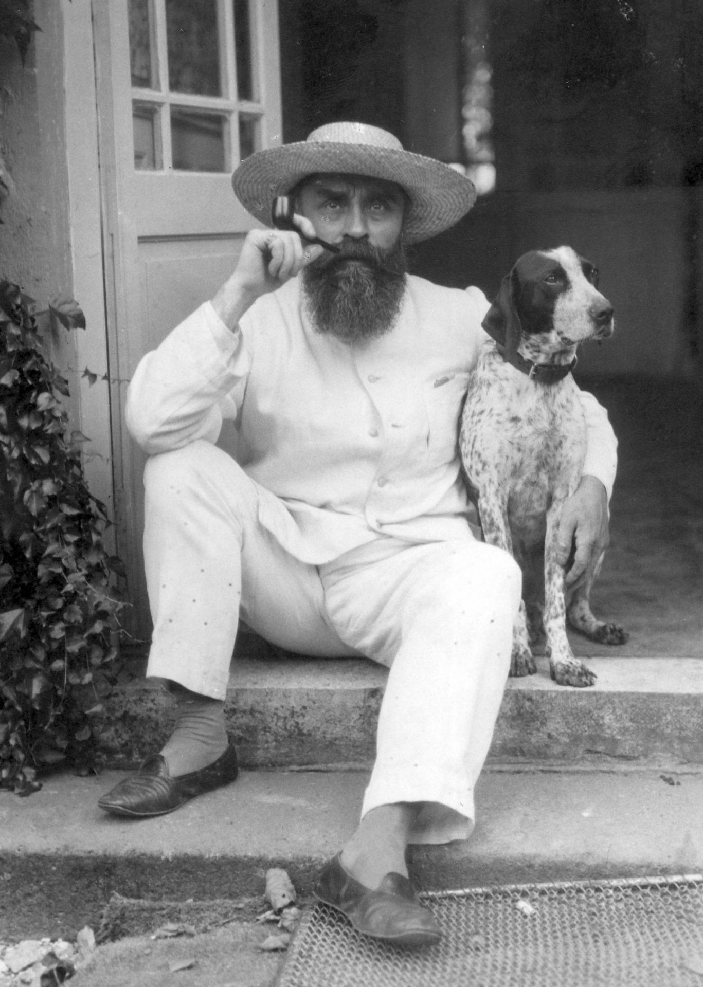 Alexandre Varenne assis sur une marche d'escalier en compagnie d'un chien